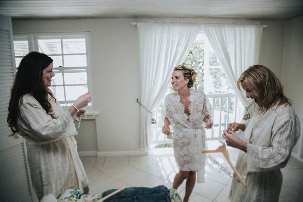 Bride laughing and joking with Bridesmaids as they get ready for wedding