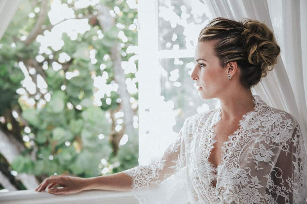Bride looking out window on morning of her wedding