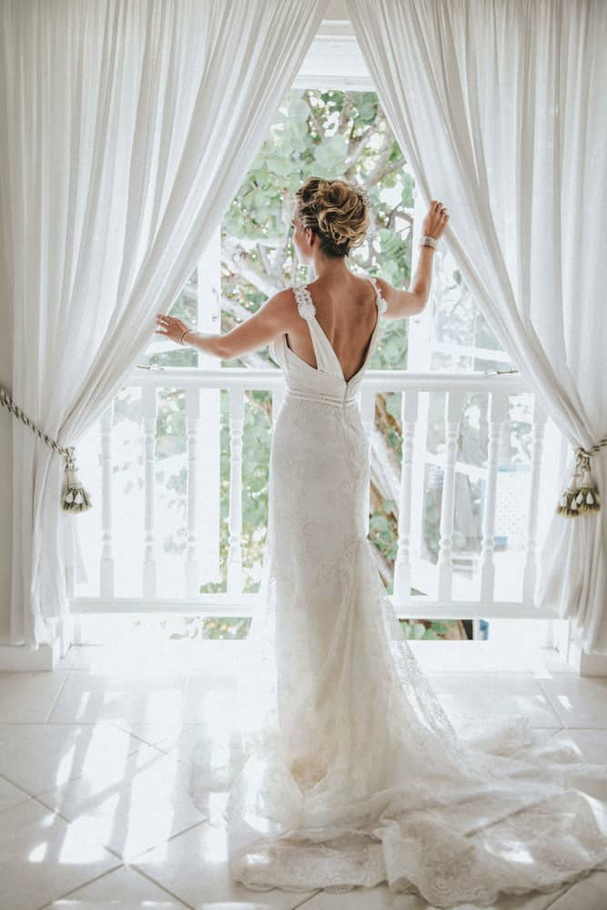 Bride looking out of window showing back detail to her exquisite wedding dress