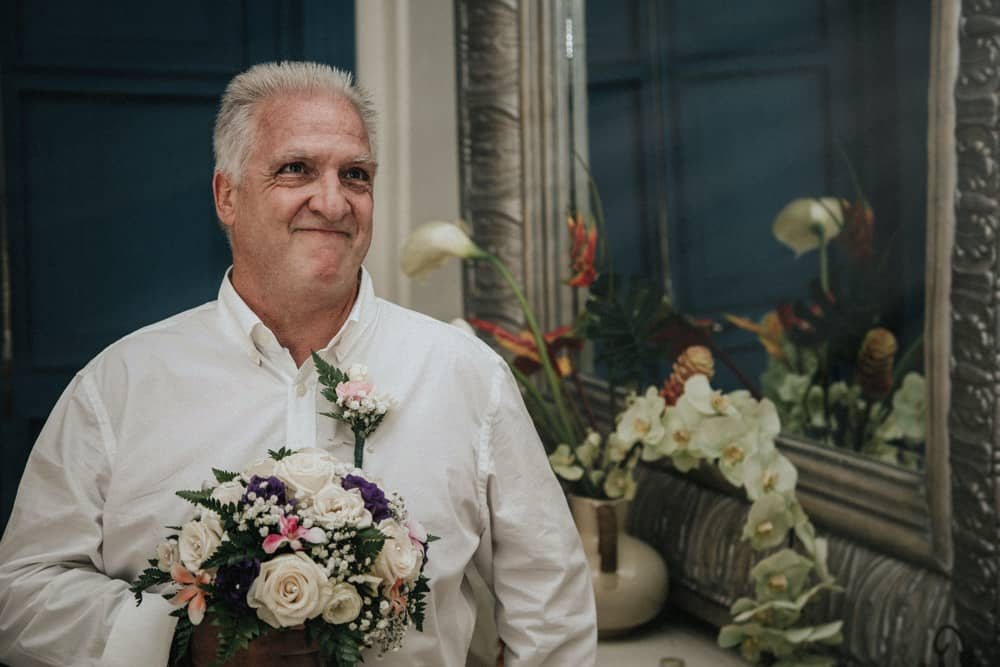 Father of Bride seeing his daughter come down the stairs for the first time in her wedding dress, holding her bouquet