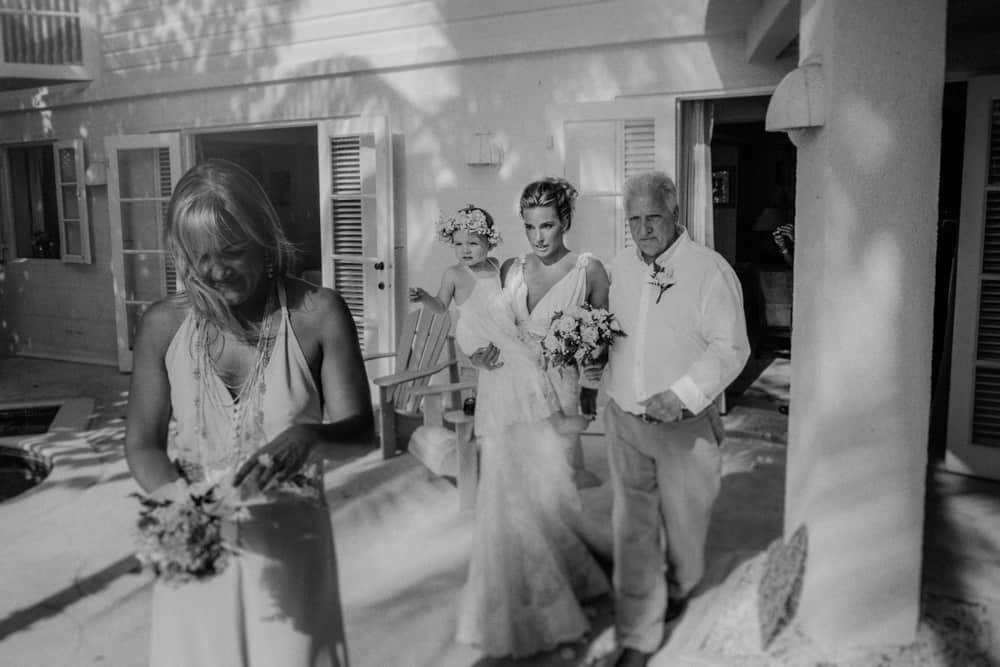 Bride, her daughter, and her father beginning the walk down the aisle to her wedding