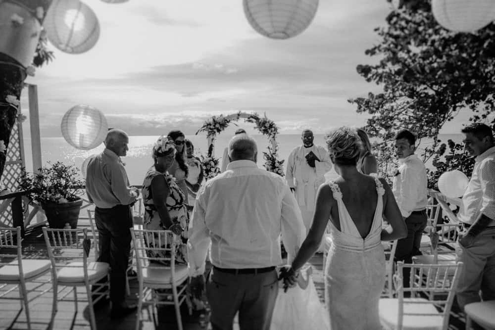 Father walking daughter down the aisle as guests onlook framed by paper lanterns and a backdrop to the sea