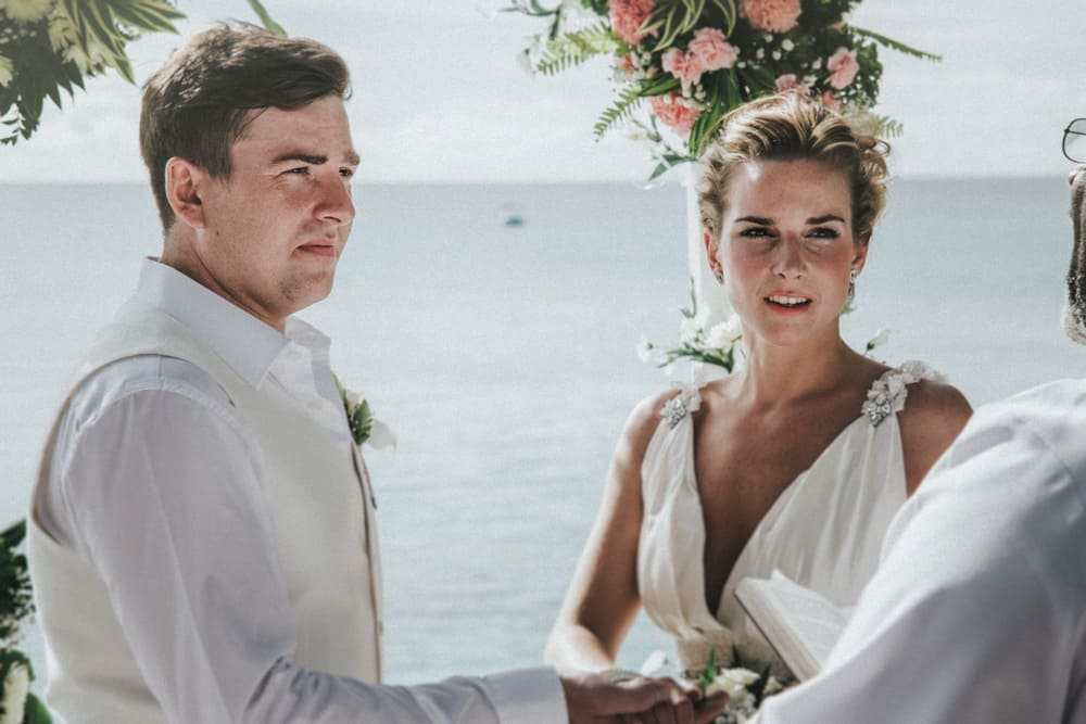 Bride & Groom listening to officiant at their wedding in Barbados with a backdrop of the sea