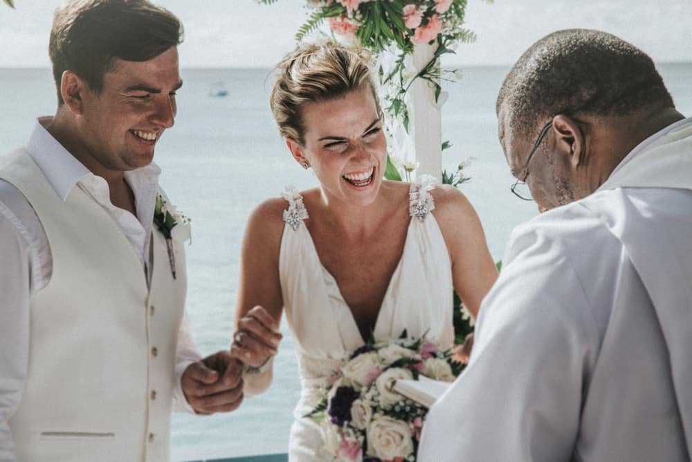 Bride & Groom laughing with wedding officiant during vows