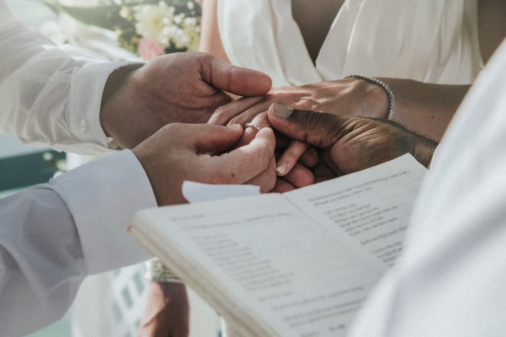 Groom placing ring on Bride's finger