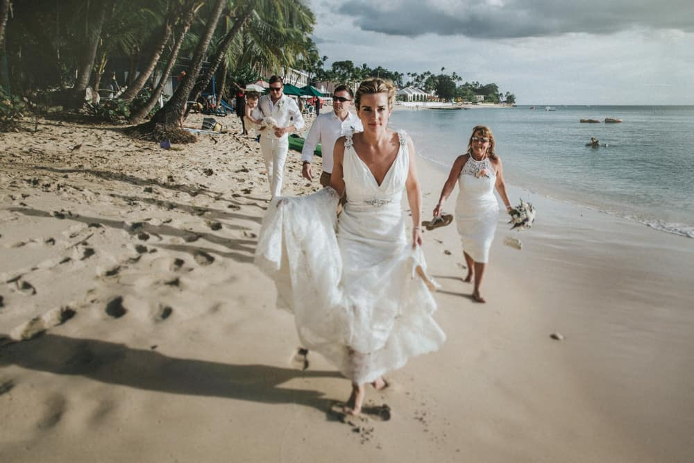 Bride, Groom and members of the Wedding party walking barefoot along Beach in Holetown, Barbados