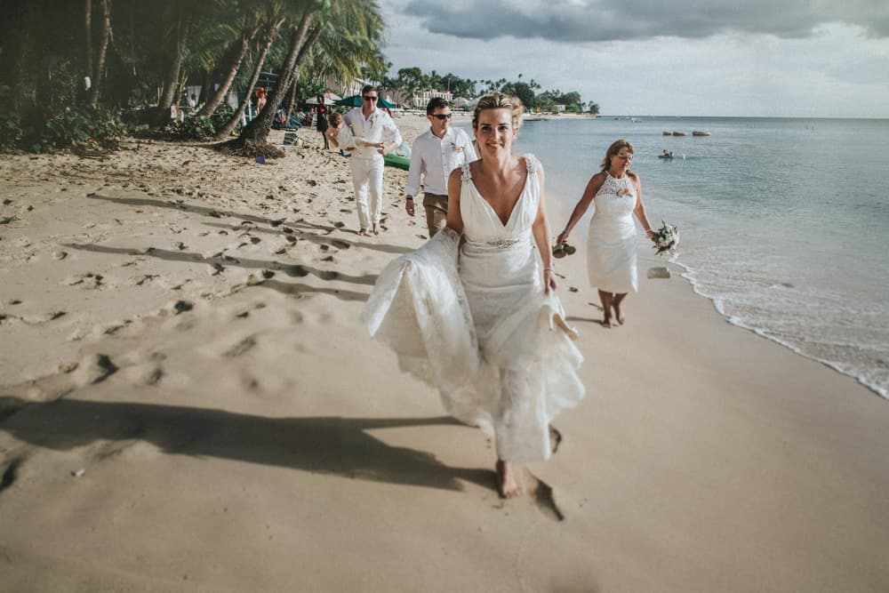 Bridal party walking along Holetown Beach, Barbados