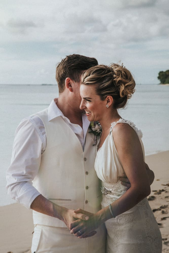 Bride & groom holding hands on a beach in Barbados