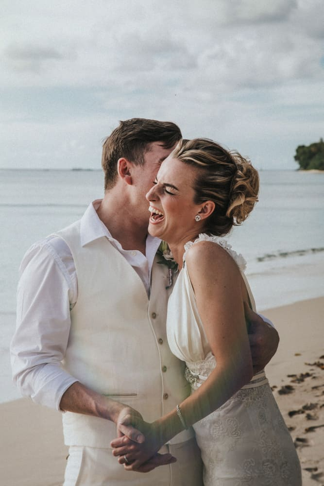 Bride and groom laughing on the beach whilst holding hands as groom whispers something in his bride's ear