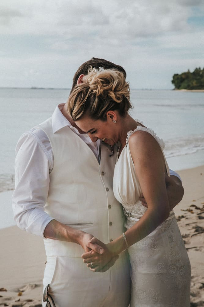 Groom whispering in Brides ear whilst holding her hand on holetown Beach, Barbados
