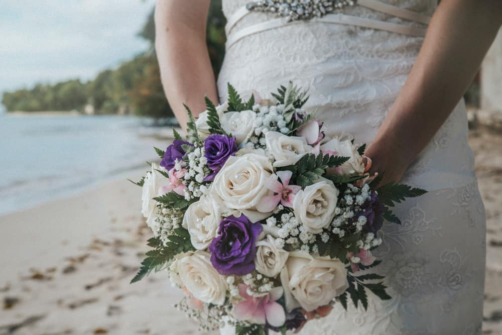 Bride hold bouquet of flowers with whites and purples