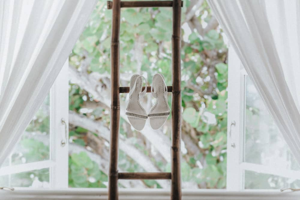 Bridal Shoes hung over a bamboo ladder