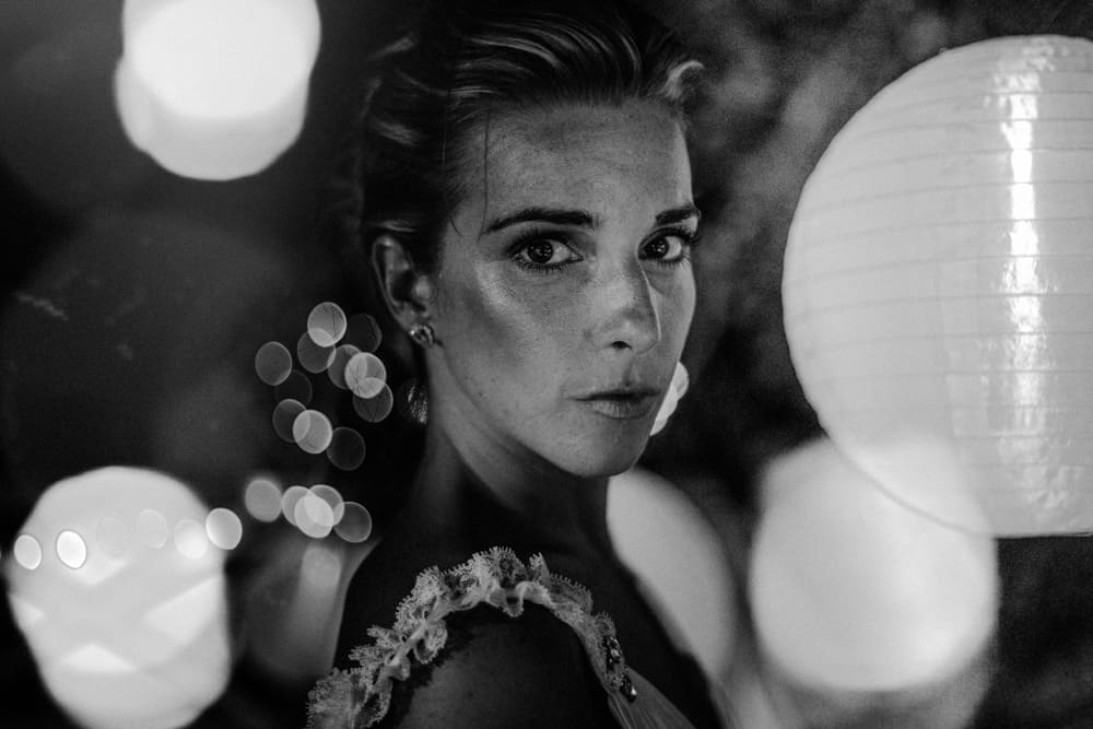 Striking Bride looking into camera surrounded by lanterns