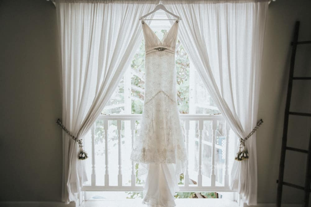 Wedding dress backlit by light from window it is hung in front of