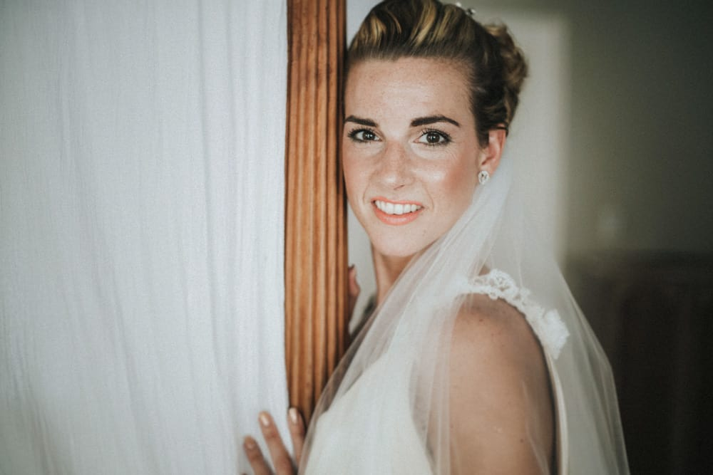 Bride leaning against 4 poster bed smiling