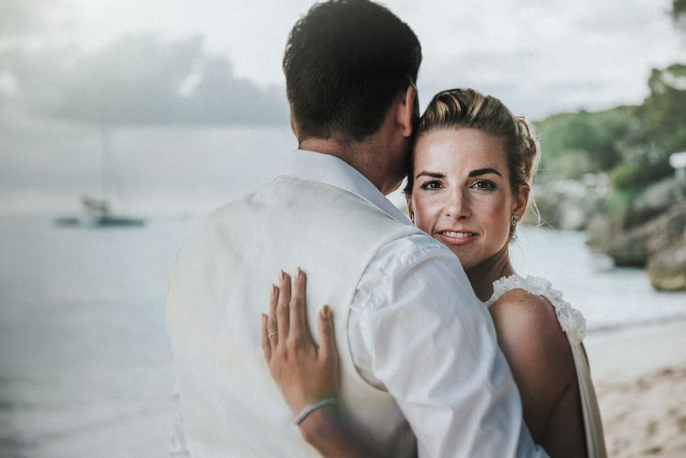 Bride and groom stood on Holetown Beach, Barbados with groom with his back to us and bride looking at camera smiling