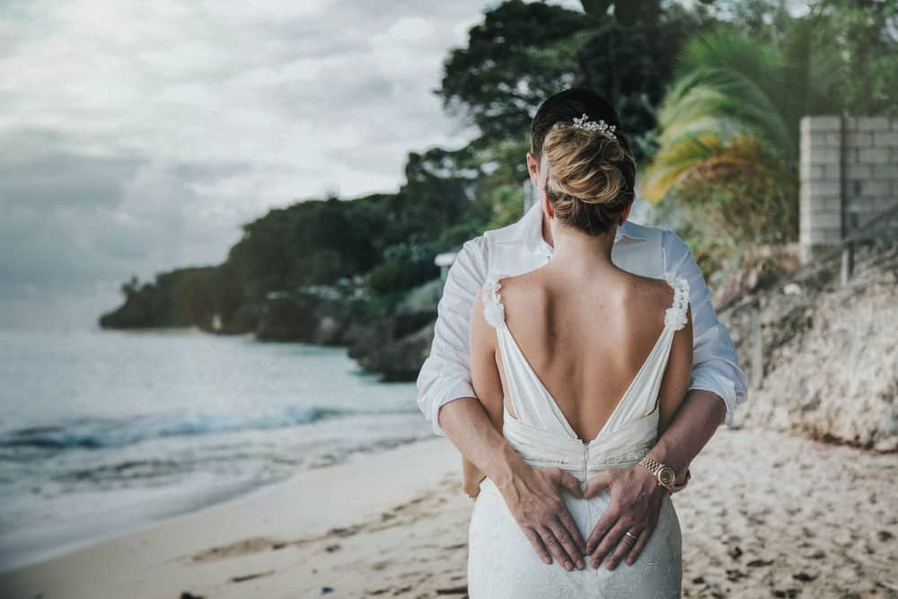 Bride & Groom embracing on Holetone, Beach in Barbados with groom forming a heart on brides back