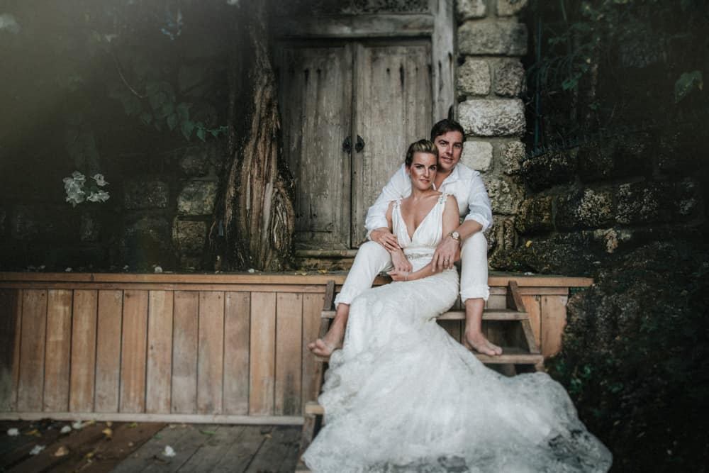 Bride & Groom sat outside of old wooden gate on wooden steps near Holetown, Barbados