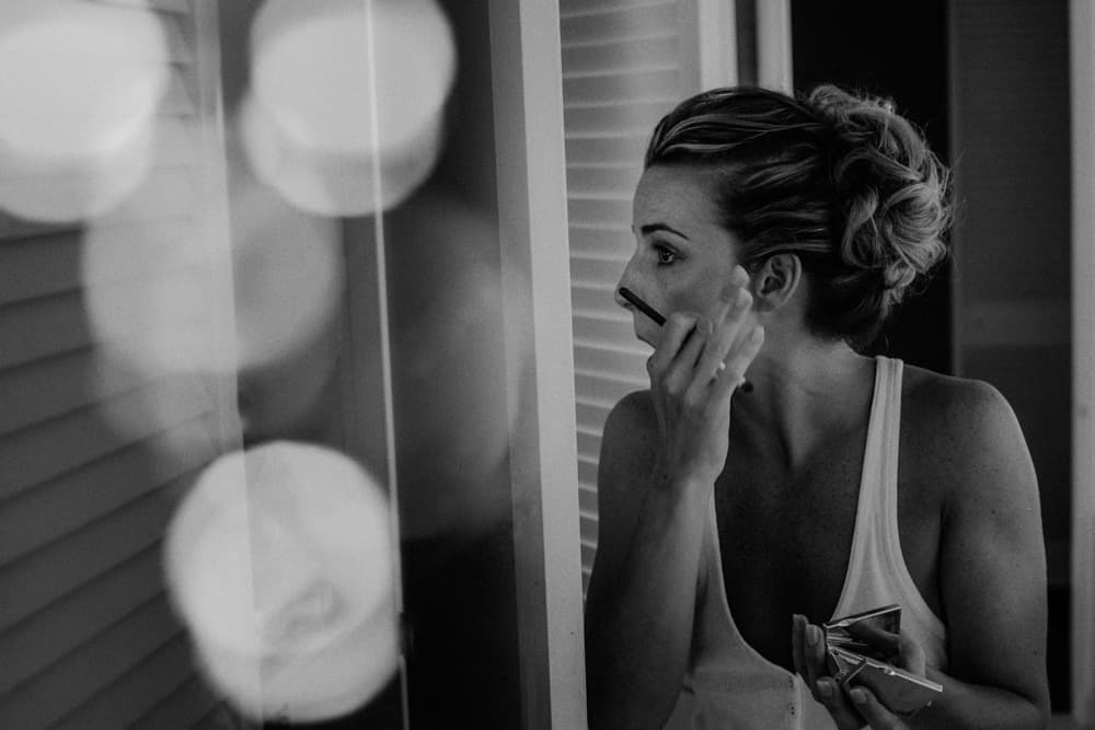 Bride applying her makeup
