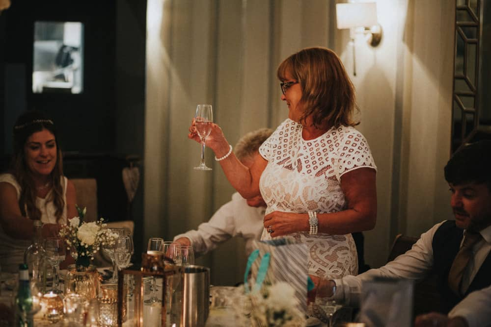 Mother of groom raising glass in toast to happy couple