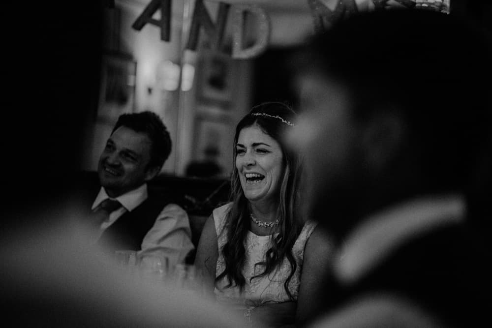 Bride laughing at small intimate wedding dinner