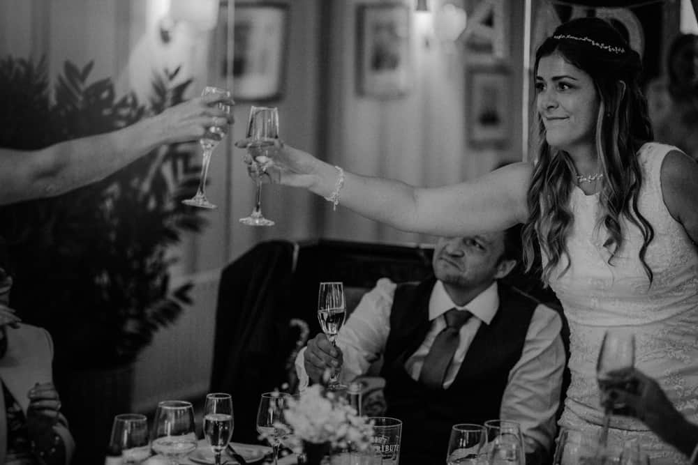 Bride toasting bridesmaid and best friend during speech as groom smiles