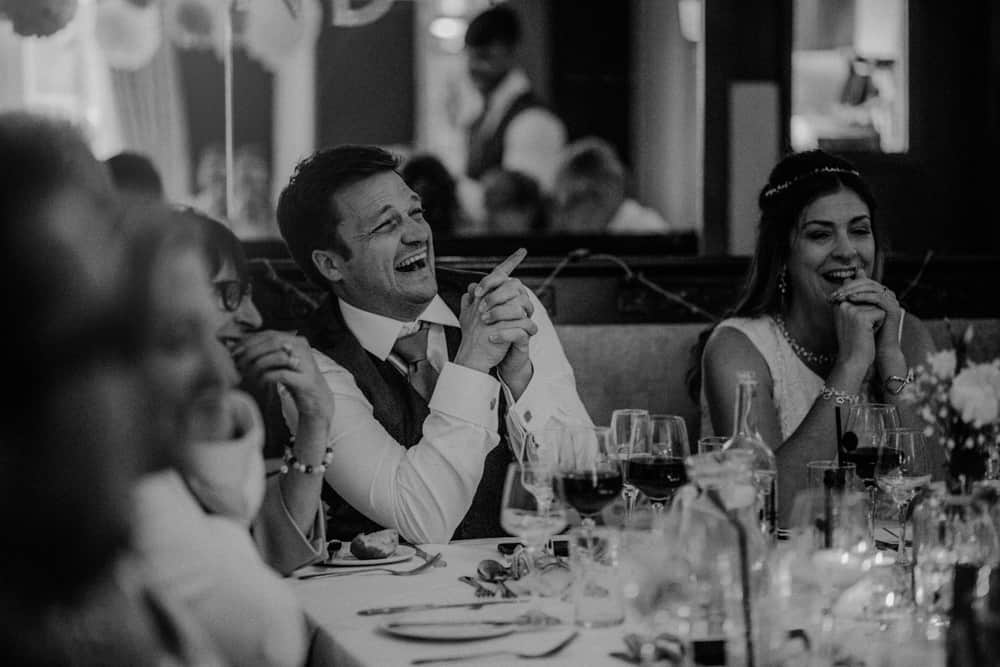 Bride & Groom laughing during speeches at small intimate wedding dinner