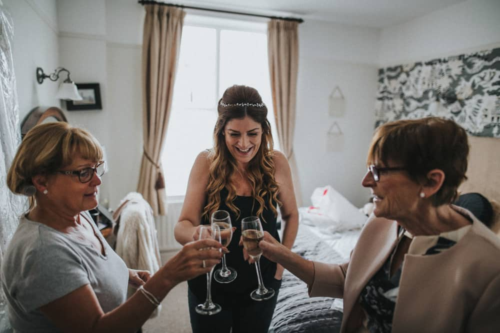 Bride toasting to her wedding day with her mother, and grooms mother