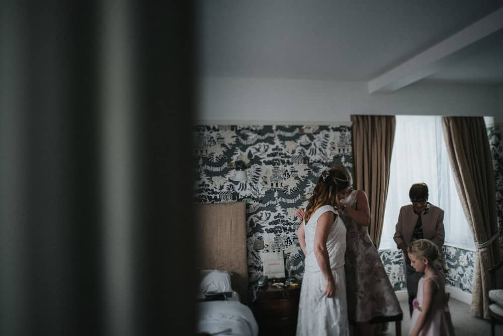 Bridesmaid helping bride into wedding dress as young girl watches
