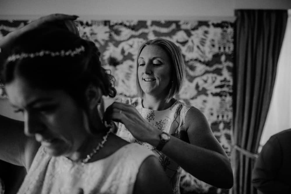Bridesmaid helping bride put on her necklace