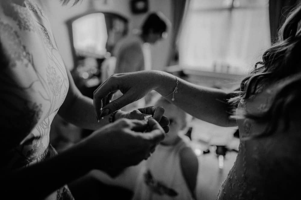 Bridesmaid helping bride put on her bracelet as young girl watches