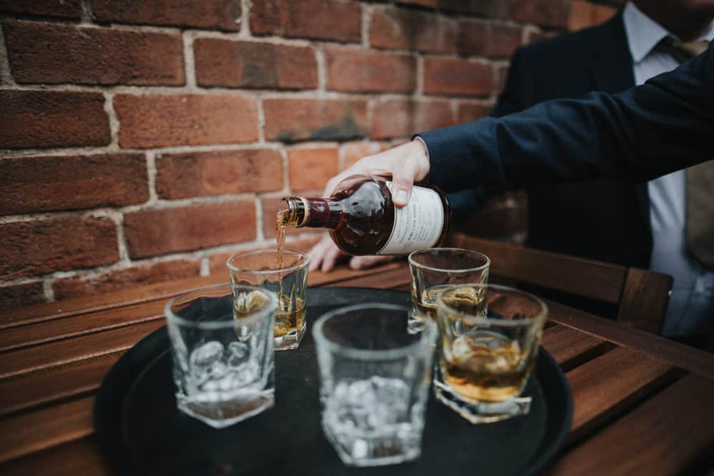 Groom pouring 5 glasses of rum for men in wedding party
