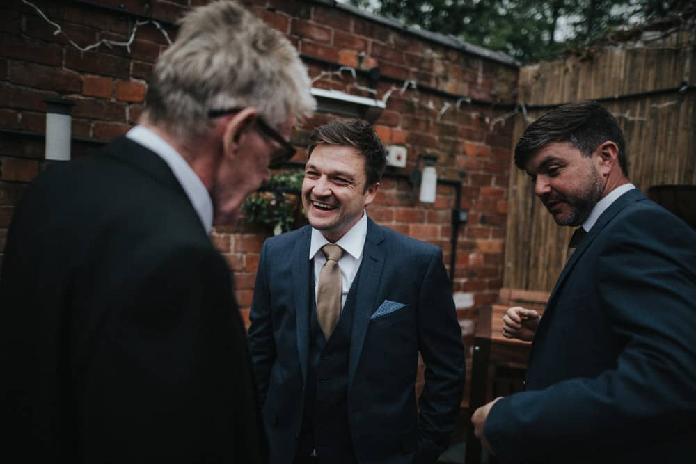 Groom and men from wedding party laughing