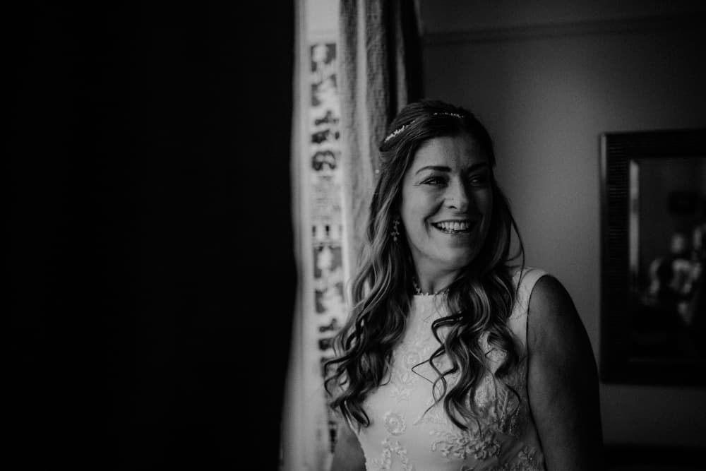 Bride stood by window laughing