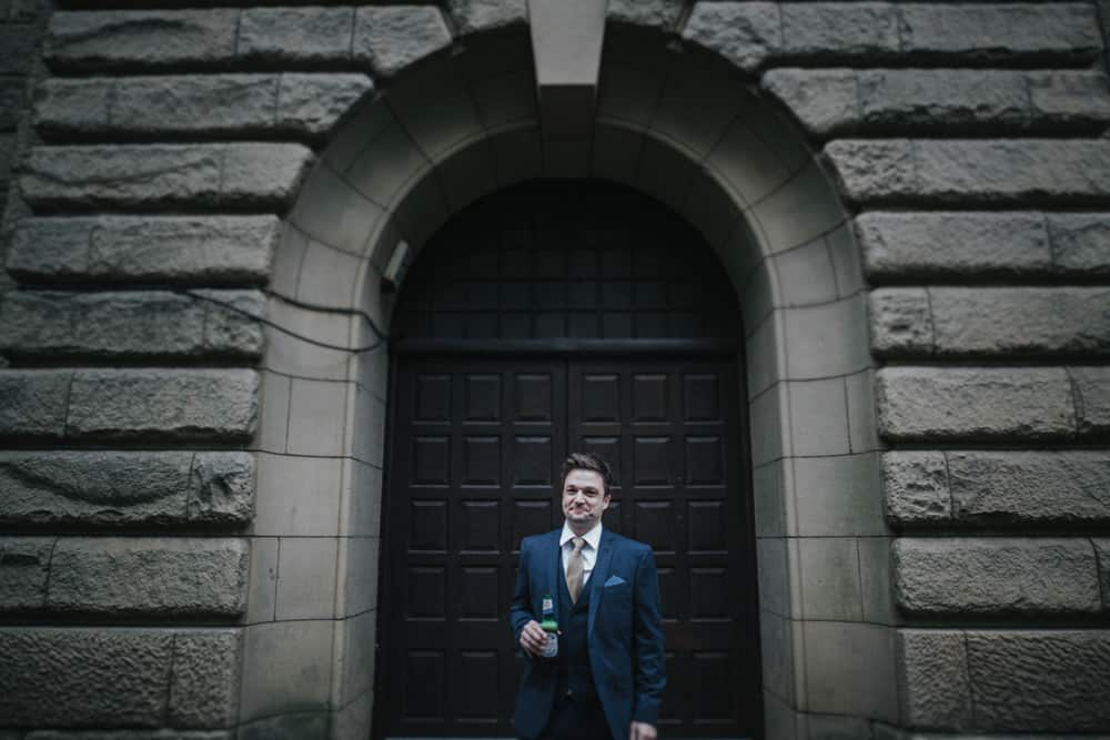 Groom stood in front of balck arched doorway drinking beer as he waits for his bride for their first look