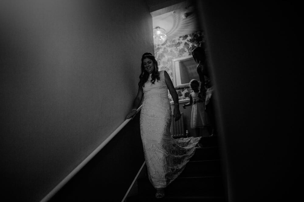 Bride descending stairs as Bridesmaids watch