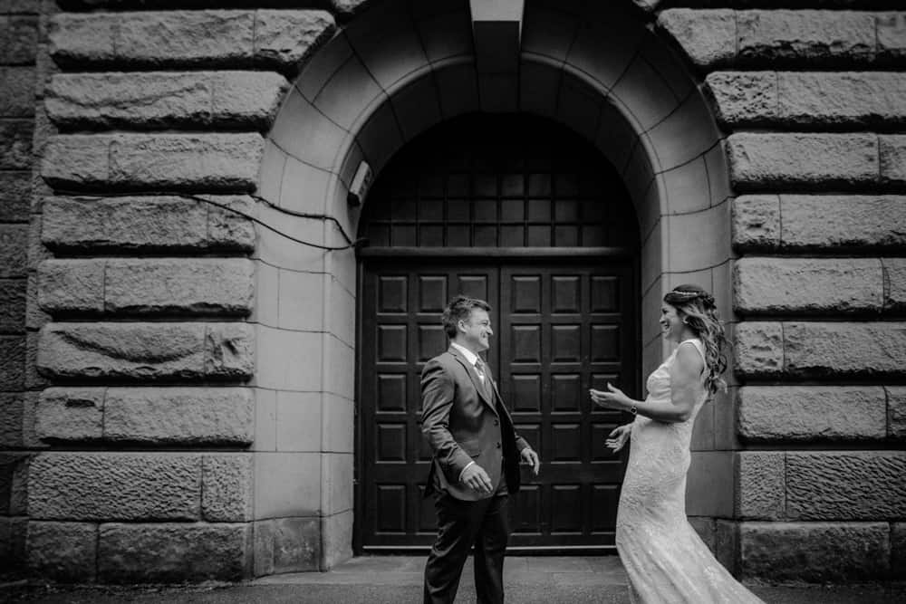 Bride & Groom's first look in front of a black arched doorway of Lincoln Tower