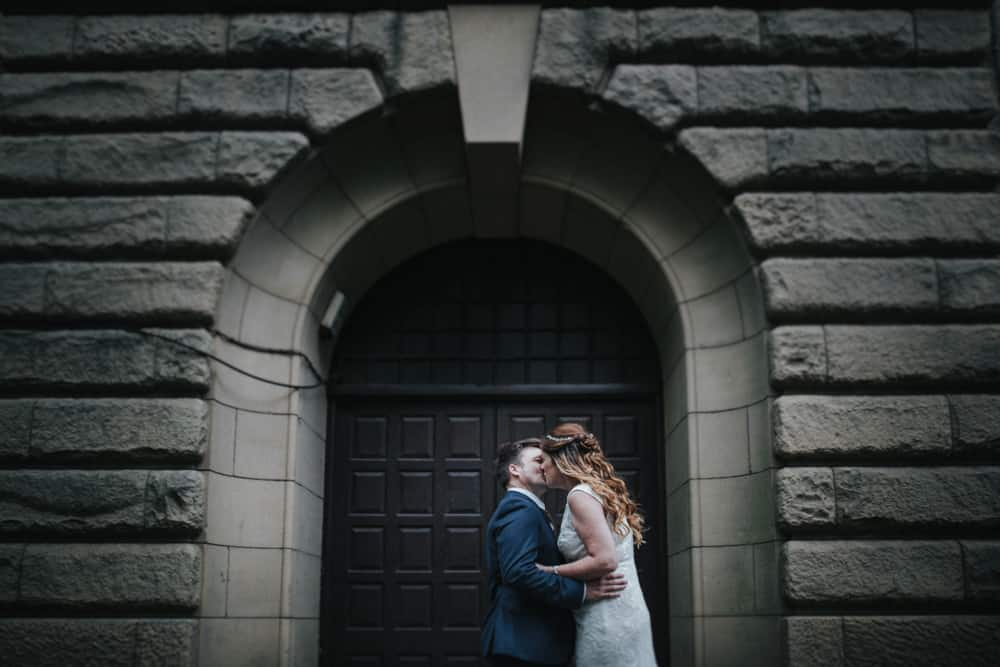 Bride & Groom kissing at first look outside the arched door of Lincoln tower