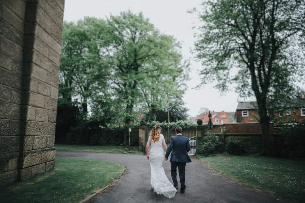 Bride & groom walking in garden of Lincoln Tower