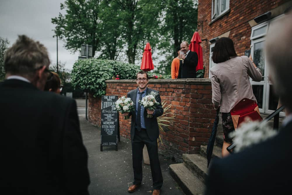 Man holding 2 bouquets outside of the Tower Hotel, Lincoln