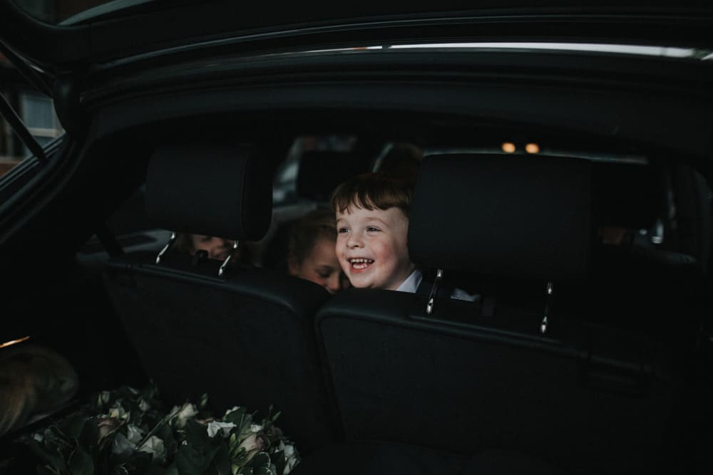 Pageboy poking head through car headrests looking out of the boot and laughing