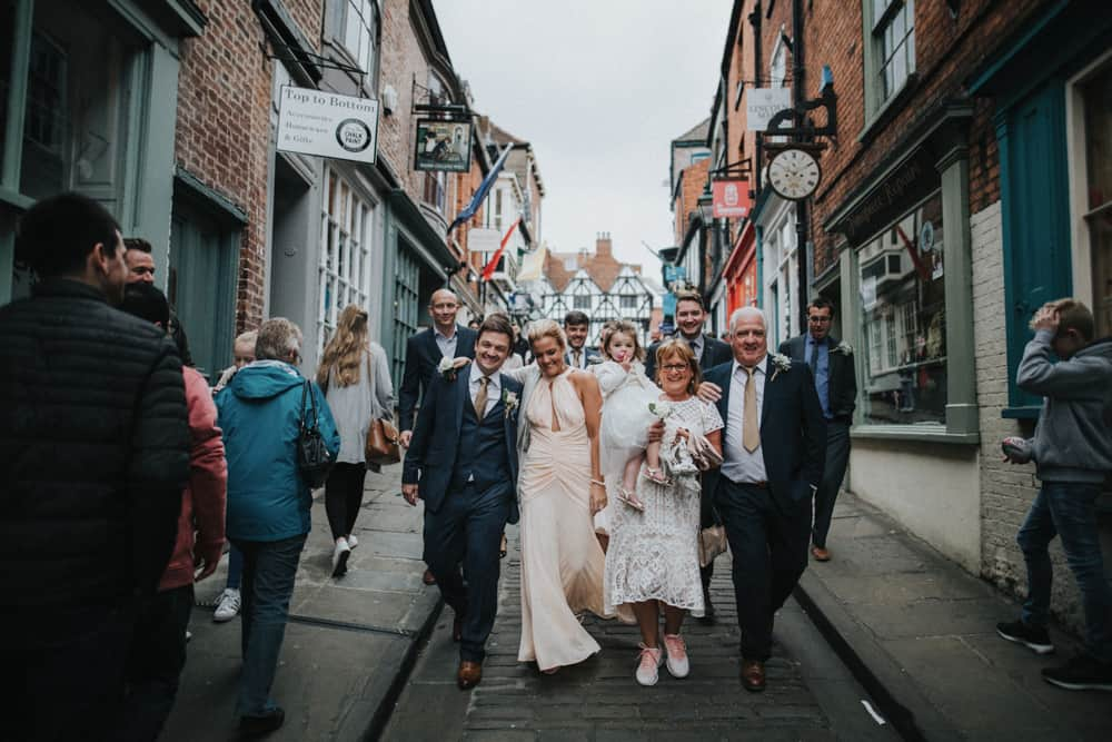 Intimate Wedding party walking to ceremony through streets of Lincoln