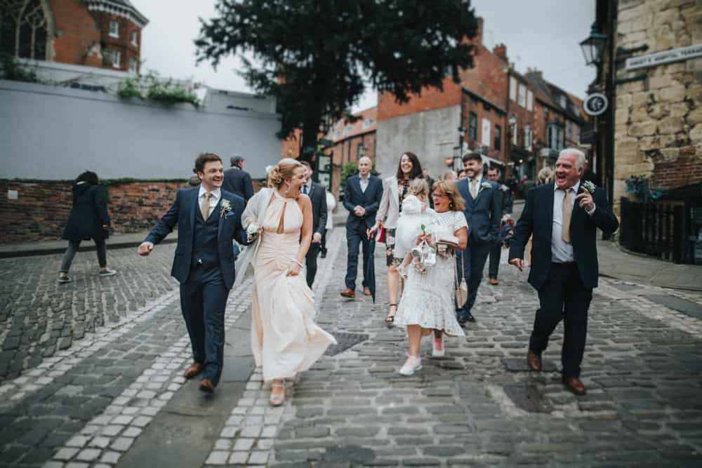Wedding party laughing as they walk to ceremony through streets of Lincoln