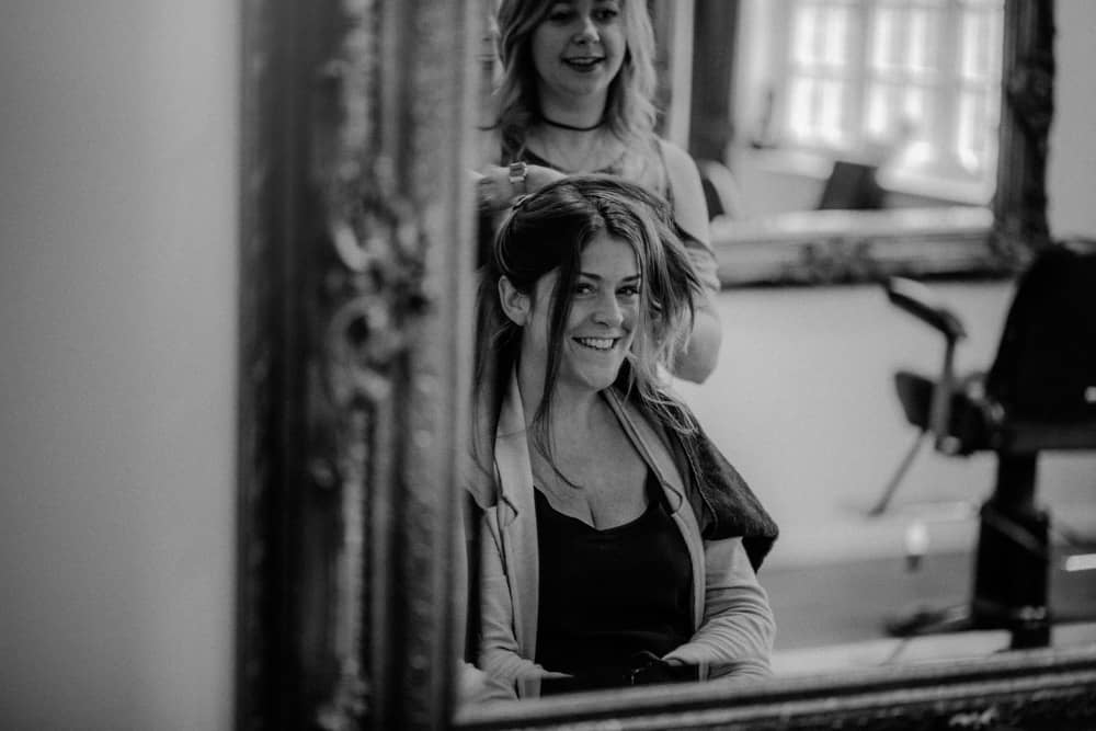 Reflection in mirror of hairdresser working on Bride's hair as she smiles