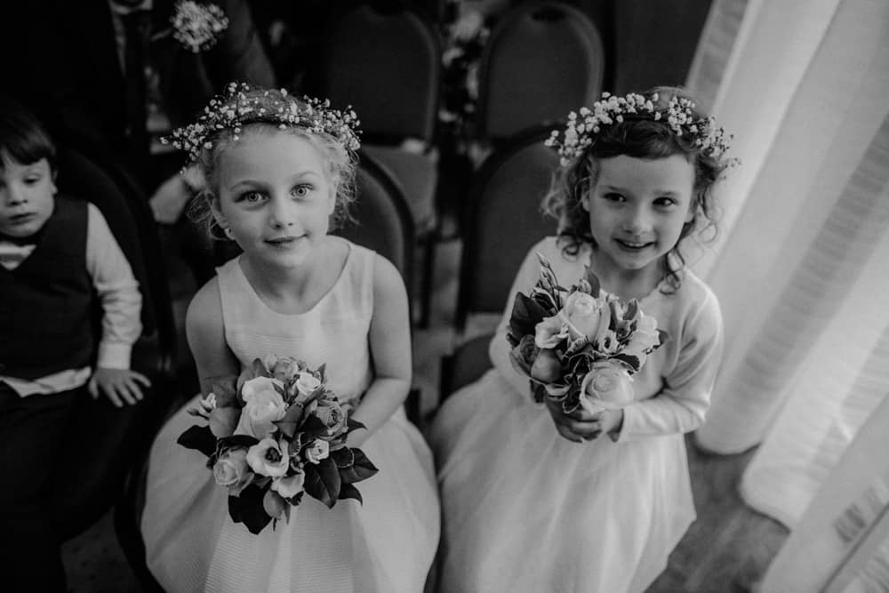 Flowergirls waiting for arrival of the bride holding their bouquets