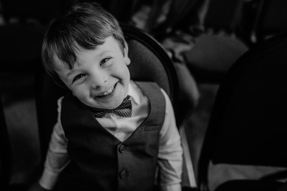 Little boy laughing and grinning at the camera as he sits waiting for arrival of the bride