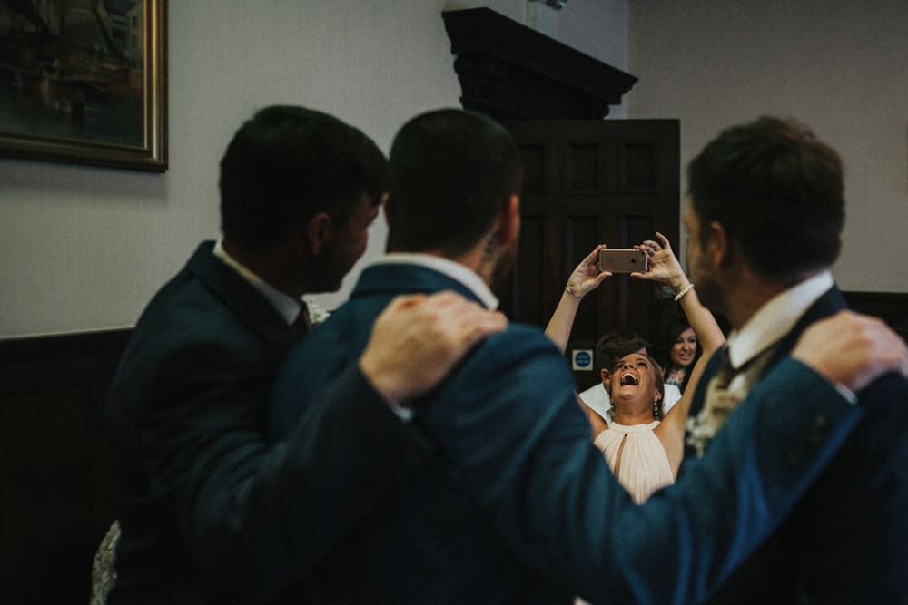 Woman taking a picture of Groomsmen with phone