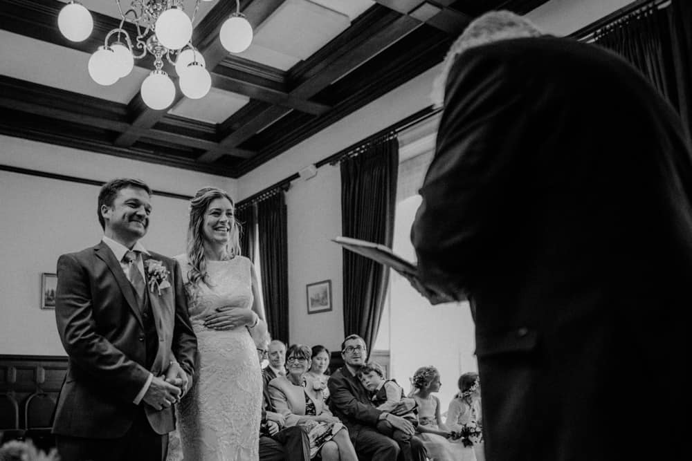 Bride & Groom holding hands during wedding ceremony as guests watch