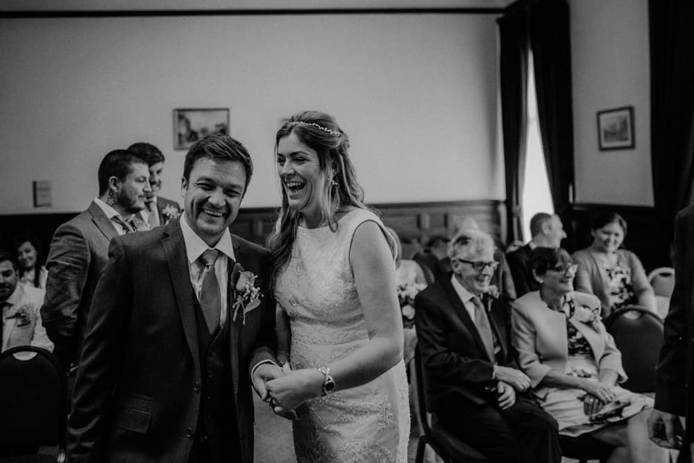 Husband and wife laughing during wedding ceremony