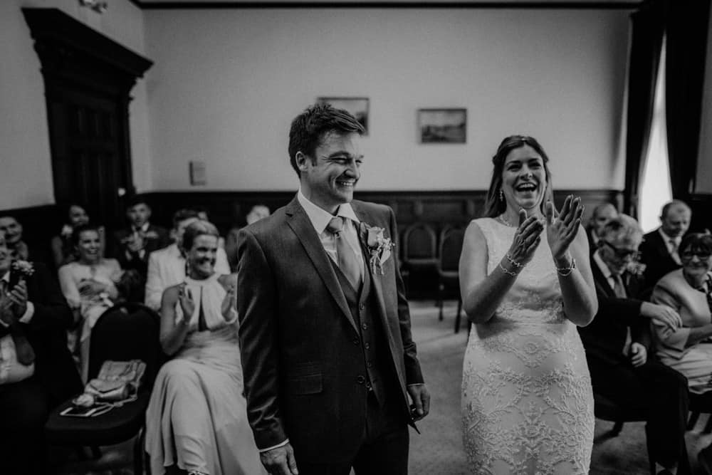 Bride clapping and laughing during her wedding ceremony as groom smiles